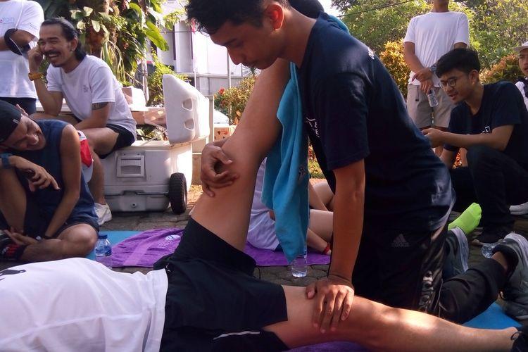 Pelari peserta program Smile Train Indonesia dibantu terapis melakukan peregangan dan pemulihan otot usai melakukan lari 30.000 meter meter di kawasan Taman Kerinci, Kebayoran Baru, Jakarta pada Sabtu (24/8/2019).