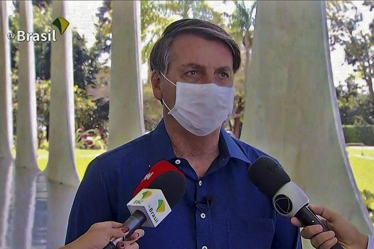 Tayangan dari TV Brasil menampilkan Presiden Brasil Jair Bolsonaro mengenakan masker saat diwawancarai wartawan di istana kepresidenan Planalto Palace di Brasilia, pada Selasa (7/7/2020). Di hari itu Bolsonaro dinyatakan positif Covid-19, tapi mengaku dirinya baik-baik saja serta hanya mengalami gejala ringan.