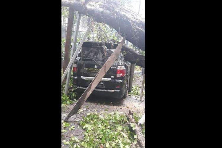 Sebuah pohon di Jalan Limau, Kramat Pela, Kebayoran Baru, Jakarta Selatan menimpa mobil milik SMA Muhammadiyah, Rabu (12/12/2018)