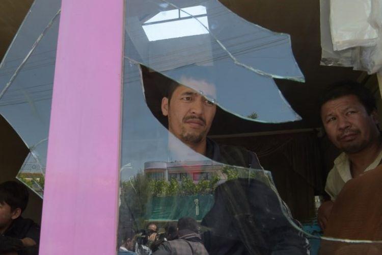 Penduduk Afghanistan memeriksa lokasi ledakan bim bunuh diri di luar pusat pendaftaran pemilih pemilu legislatif di Kabul, Minggu (22/4/2018). (AFP/Shah Marai)