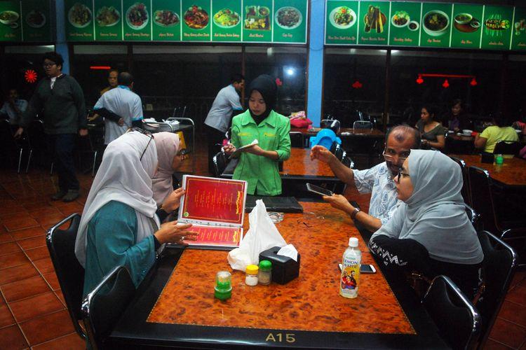 Seorang karyawan rumah makan Rindu Alam, Cisarua, Puncak, Bogor, Jawa Barat, sedang melayani pelanggan turis arab yang datang, Kamis (30/11/2017).