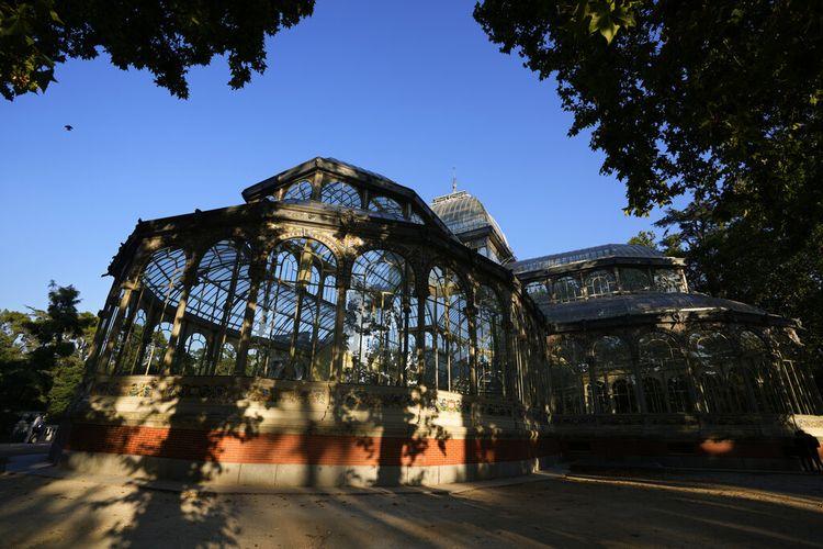 Istana Kaca berdiri dinaungi pepohonan di taman Retiro di Madrid, Spanyol, Kamis, 22 Juli 2021.