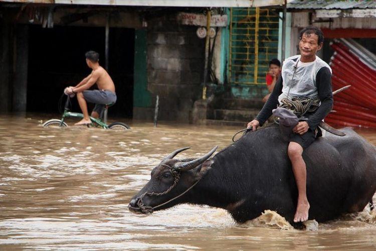 Masyarakat melewati jalan yang banjir di kota Baao di provinsi Camarines Sur pada Minggu (30/12/2018), usai badai Usman melanda wilayah di Filipina pada Sabtu (29/12/2018). (AFP/Simvale Sayat)