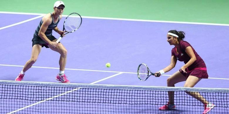 Pasangan ganda putri, Cara Black (kiri)/Sania Mirza, mengembalikan bola dari pasangan Hsieh Su-wei/Peng Shuai, pada final ganda putri WTA FInal di ingapore Indoor Stadium, Minggu (26/10/2014). Black/Mirza menang 6-1, 6-0.