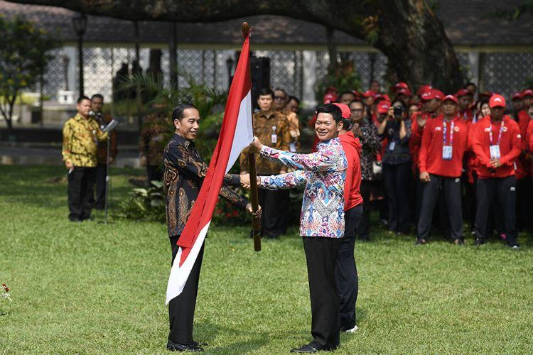 Presiden Joko Widodo (kiri) menyerahkan bendera Merah Putih kepada Ketua Inapgoc Raja Sapta Oktohari (kanan) saat upacara pelepasan kontingen Indonesia untuk Para Games ke-3 Tahun 2018 di halaman tengah Istana Kepresidenan, Jakarta, Selasa (2/10/2018). Presiden melepas 296 atlet dari 18 cabang olahraga yang akan berlaga dalam Asian Para Games ke-3 Tahun 2018 pada 6-13 Oktober mendatang.