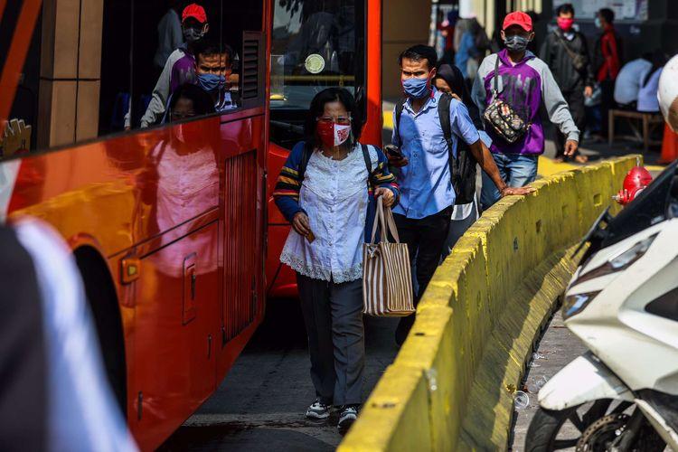 Pekerja menggunakan masker saat memasuki bus transjakarta di Kawasan Tanah Abang, Jakarta Pusat, Senin (21/9/2020). PSBB kembali diterapkan tanggal 14 September 2020, berbagai aktivitas kembali dibatasi yakni aktivitas perkantoran, usaha, transportasi, hingga fasilitas umum.