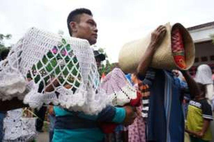 Keluarga membawa bantal dan tikar saat mengarak pengantin dalam tradisi jolang di Desa Olehsari, Kabupaten Banyuwangi, Jawa Timur, Minggu (27/11/2016).