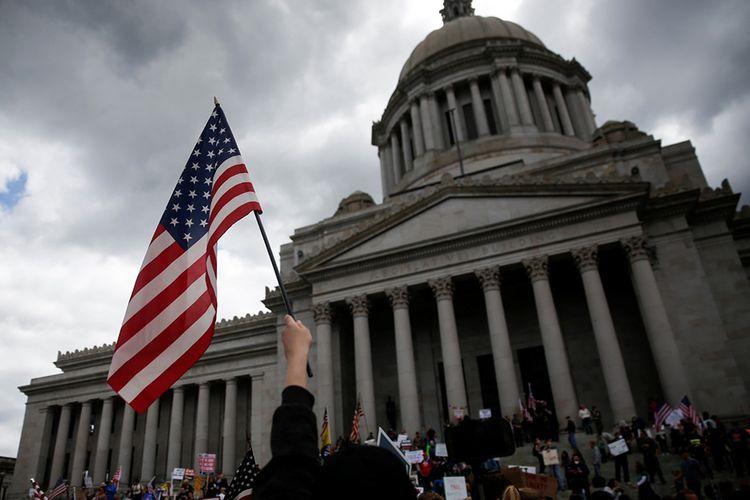 Seorang warga mengibarkan bendera Amerika saat protes atas perpanjangan perintah tetap berada di rumah untuk memperlambat penyebaran penyakit virus corona (Covid-19) di gedung Capitol di Olympia, Washington, Amerika Serikat, Minggu (19/4/2020). Berdasarkan data Johns Hopkins University, hingga Selasa (21/4/2020), AS masih menjadi negara dengan kasus Covid-19 tertinggi dunia mencapai 787.794 dengan korban meninggal 42.362.