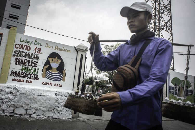 Pedagang yang tidak mengenakan masker berjalan di depan mural yang berisi pesan waspada virus Corona di Petamburan, Jakarta, Rabu (16/9/2020). Mural tersebut dibuat untuk mengingatkan masyarakat agar menerapkan protokol kesehatan saat beraktivitas karena masih tingginya angka kasus COVID-19 secara nasional. ANTARA FOTO/Aprillio Akbar/aww.