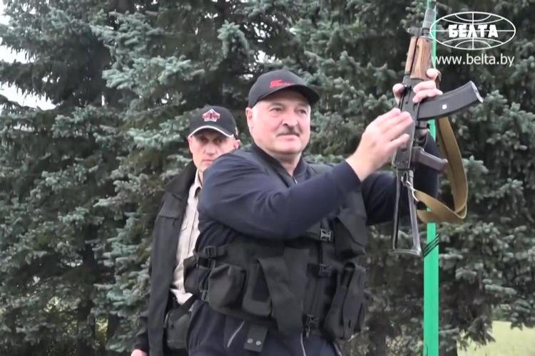 Tangkapan layar dari video yang dirilis media pemerintah Belarus BELTA, menunjukkan Presiden Belarus Alexander Lukashenko memegang senapan laras panjang otomatis dan mengenakan rompi antipeluru, saat hendak membubarkan massa dari kediamannya pada Minggu (23/8/2020).