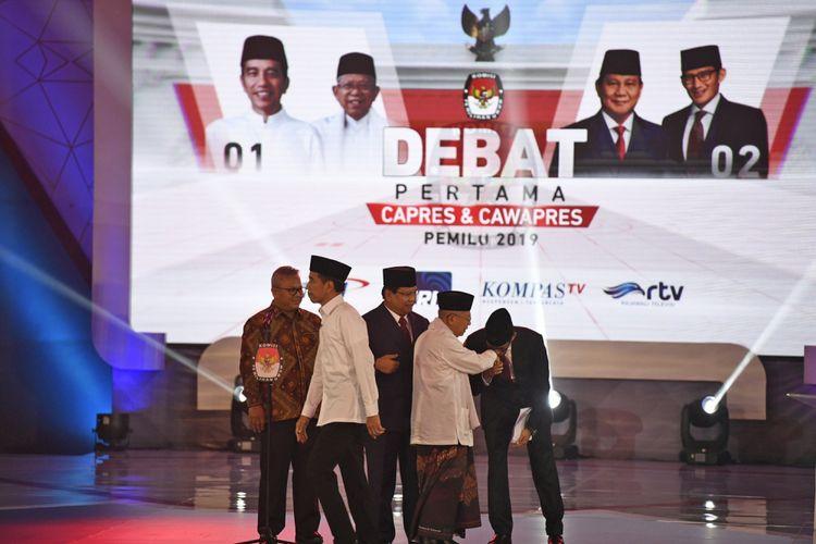 Ketua KPU Arief Budiman (kiri) bersama pasangan capres-cawapres nomor urut 01 Joko Widodo (kedua kiri) dan Maruf Amin (kedua kanan) serta pasangan nomor urut 02 Prabowo Subianto (tengah) dan Sandiaga Uno (kanan) bersiap mengikuti debat pertama Pilpres 2019, di Hotel Bidakara, Jakarta, Kamis (17/1/2019). Debat tersebut mengangkat tema Hukum, HAM, Korupsi, dan Terorisme.