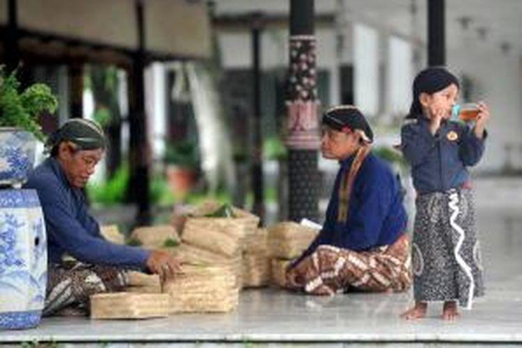 Rizky (2 tahun, kanan) menemani kakeknya, abdi dalem Cermo Wicoro (kiri) yang sedang bertugas di Keraton Yogyakarta, Yogyakarta, Senin (4/4/2011). Mengabdikan diri untuk Keraton Yogyakarta telah menjadi pilihan hidup baginya dengan harapan hadirnya limpahan berkah bagi keluarga mereka. KOMPAS/FERGANATA INDRA RIATMOKO
