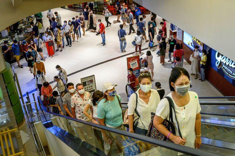 Pengunjung mengantre untuk menaiki eskalator di mal Siam Paragon, Bangkok, Thailand, Minggu (17/5/2020). Mal-mal di Thailand dibuka lagi setelah angka penularan Covid-19 melambat.