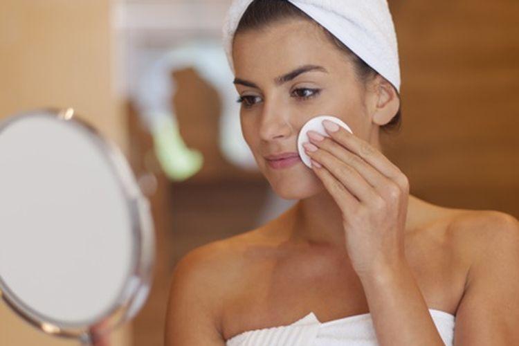 Ilustrasi perempuan membersihkan wajah menggunakan kapas.