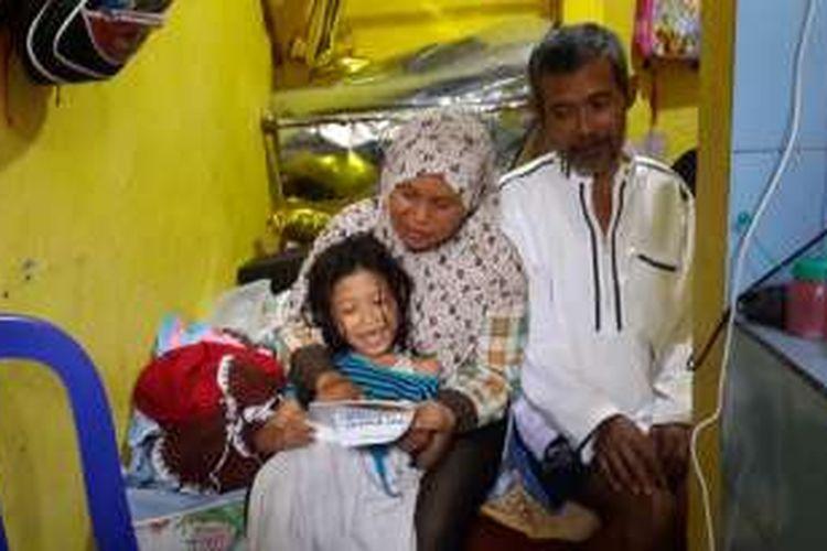 Sriana (41) saat mengajari anak bungsunya membaca didampingi suaminya, Suwarno (55) yang sakit saraf dan tidak bisa apa - apa, Minggu (24/7/2016) di rumahnya, Jalan Muharto gang 6 nomor 13 RT 13 RW 7 Kelurahan Jodipan, Kecamatan Blimbing, Kota Malang, Jawa Timur