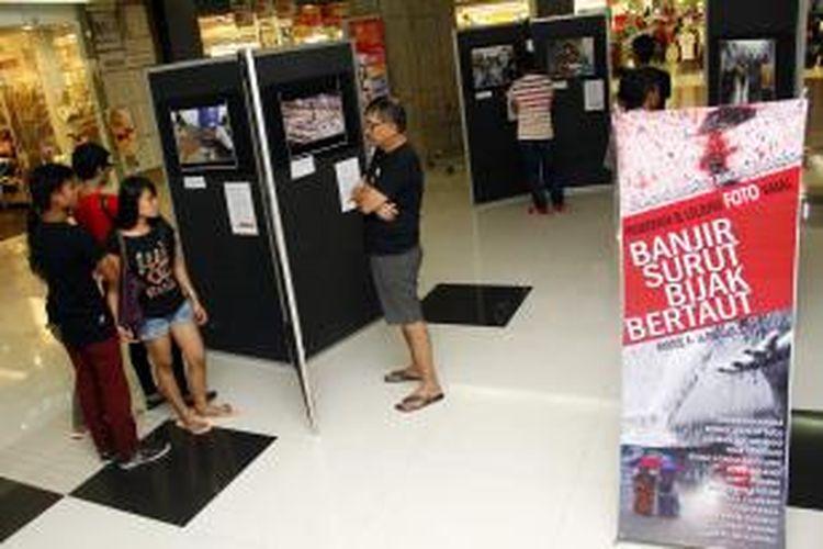 Pengunjung sedang melihat-lihat foto-foto mengenai bencana banjir di Manado yang sedang dipamerkan dalam Pameran dan Lelanf Foto Amala,