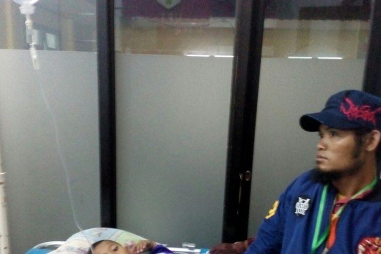 M Aldi (8), salah satu anak yang jadi korban keracunan massal ditunggui oleh ayahnya saat dirawat di Puskesmas DTP Bayongbong.
