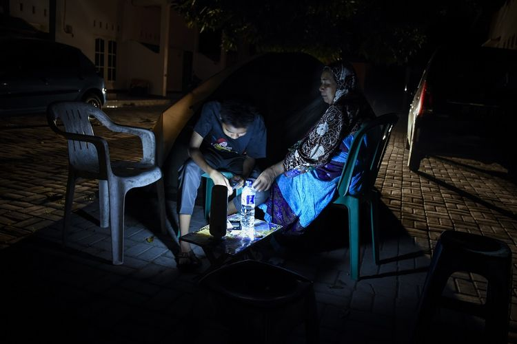 Warga memilih tetap berada diluar rumah pascagempa di Ampenan, Mataram, NTB, Minggu (19/8/2018). Gempa bumi berkekuatan 7 Skala Richter kembali mengguncang Lombok pada Minggu malam pukul 22.56 Wita yang berpusat di timur laut Lombok Timur pada kedalaman 10 km.