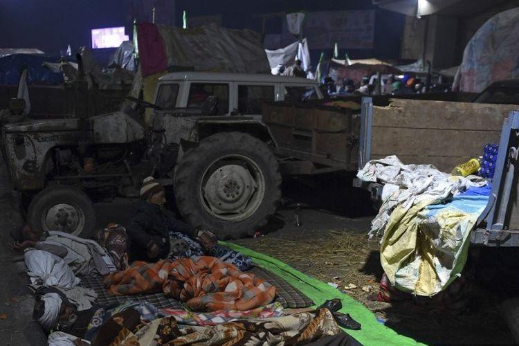 Demonstan petani India, berkemah di tempat terbuka dengan traktor dan trailer yang diparkir berdempetan melawan musim dingin yang keras di India Utara