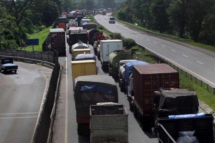 Mobil terjebak macet tol Jakarta-Merak di Balaraja Timur, Serang, Banten, akibat banjir luapan Sungai Ciujung yang merendam tol di kilometer 57, Kamis (10/1/2013). Akibat banjir ini akses tol Jakarta-Merak putus dan ratusan rumah warga terendam. KOMPAS IMAGES/KRISTIANTO PURNOMO