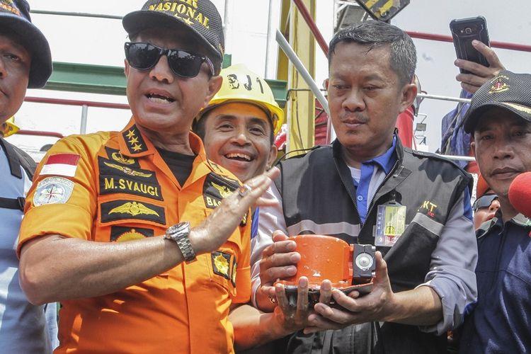 Kepala Basarnas Marsekal Madya TNI Muhammad Syaugi (kedua kiri) menunjukkan bagian dari kotak hitam (black box) pesawat Lion Air bernomor registrasi PK-LQP dengan nomor penerbangan  JT 610 yang telah ditemukan oleh tim SAR gabungan di KR Baruna Jaya I, di perairan Tanjung Karawang, Jawa Barat, Kamis (1/11/2018). Bagian dari kotak hitam tersebut diserahkan ke pihak KNKT untuk dilakukan investigasi lebih lanjut. ANTARA FOTO/Muhammad Adimaja/wsj.