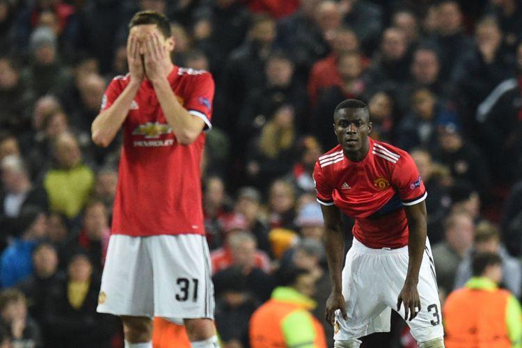 Nemanja Matic dan Eric Bailly tampak terpukul seusai Sevilla mencetak gol kedua ke gawang Manchester United pada babak 16 besar Liga Champions di Stadion Old Trafford, Selasa (13/3/2018).