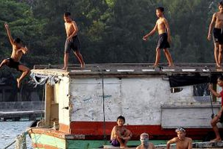 Anak-anak nelayan di Pulau Panggang, Kepulauan Seribu, Kamis (11/6/2015), bermain di atas perahu dan kapal yang tertambat di dekat dermaga. Suasana riang dan guyub seperti ini menawarkan sensasi tersendiri bagi pengunjung Pulau Panggang.
