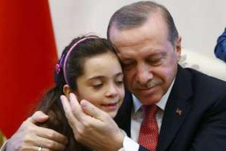 Presiden Turki Recep Tayyip Erdogan memeluk Bana Al-Abed, (7 tahun), di Istana Presiden di Ankara, Turki, Selasa (21/12/2016).