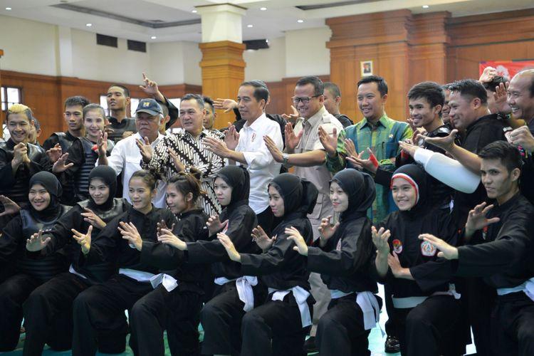 Presiden Joko Widodo (tengah) didampingi Menteri PUPR Basuki Hadimuljono (kelima kiri), Menpora Imam Nahrawi (keempat kanan) dan Ketua Harian Pengurus Besar Ikatan Pencak Silat Indonesia (IPSI) Edhy Prabowo (kelima kanan) berpose dengan atlet dan ofisial pelatnas pencak silat di Padepokan Pencak Silat TMII, Jakarta, Senin (6/8/2018). Presiden optimistis atlet pencak silat akan memperoleh lebih dari dua medali emas pada ajang Asian Games 2018.