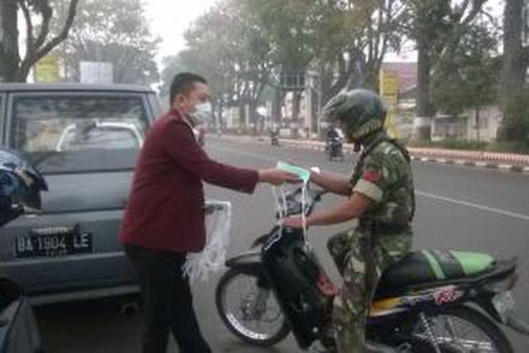 Anggota Persatuan Perawat Nasional Indonesia (PPNI) Kota Bukittinggi membagikan masker di Jalan Sudirman, Jumat (28/02/2013).