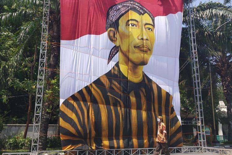 Lukisan berukuran raksasa Presiden Jokowi terpasang di depan pintu masuk utama Stadion Manahan Solo, Jawa Tengah, Minggu (20/10/2019).