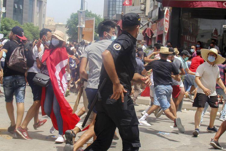 Petugas polisi Tunisia bentrok dengan pengunjuk rasa selama demonstrasi di Tunis, Tunisia, Minggu (25/7/2021). Demonstrasi disertai kekerasan pecah pada Minggu di beberapa kota Tunisia. Pengunjuk rasa menyatakan kemarahan pada memburuknya situasi kesehatan, ekonomi, dan sosial negara itu.