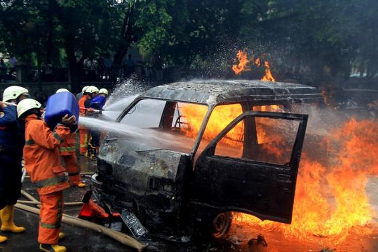 Petugas berusaha memadamkan mobil Daihatsu Zebra B2791AJ yang terbakar di Jalan Trunojoyo, samping Mabes Polri, Kebayoran Baru, Jakarta, Rabu (4/2/2015). Mobil itu membawa lima tangki berisi ratusan liter bahan bakar minyak.