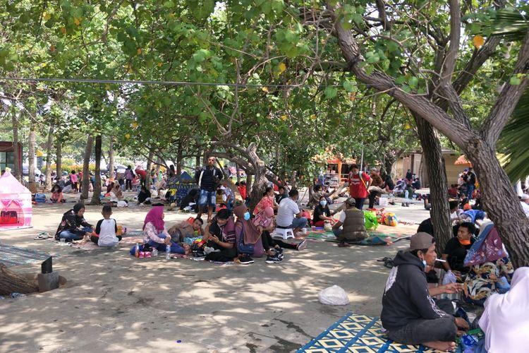 Kawasan wisata Taman Impian Jaya Ancol, tepatnya di Pantai Timur, ramai dikunjungi wisatawan pada hari pertama Idul Fitri, Kamis (13/5/2021).