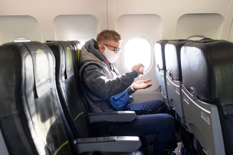 ILUSTRASI - Penumpang pesawat memakai masker dan menggunakan hand sanitizer