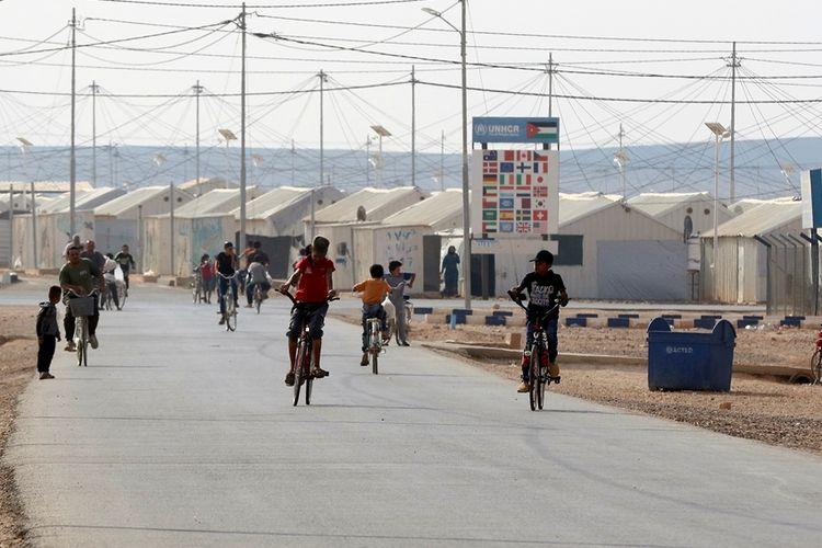 Anak-anak Suriah bersepeda di sekitar kamp pengungsian di utara Yordania.