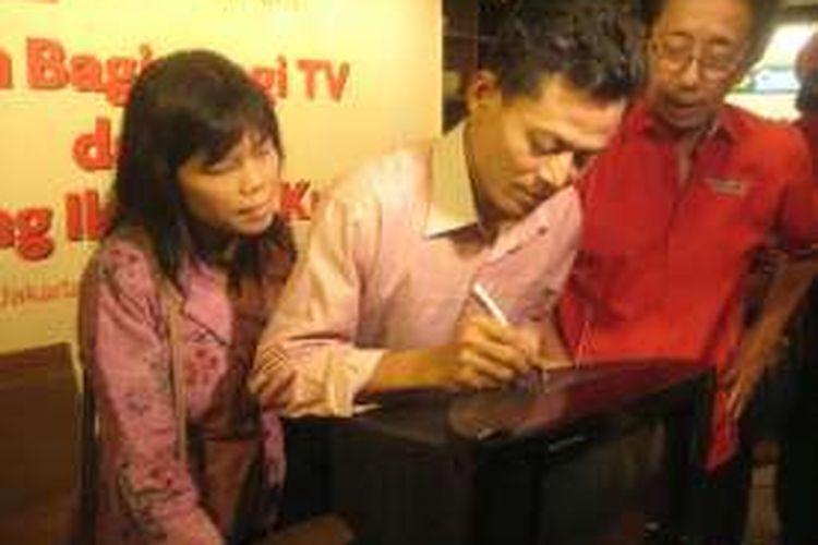 Dari kiri ke kanan, Siti Aminah (istri Kusrin), Kusrin, dan Direktur Utama PT Sido Muncul Tbk Irwan Hidayat saat penandatanganan pada salah satu televisi hasil rakitan Kusrin, Jumat (5/2/2016).