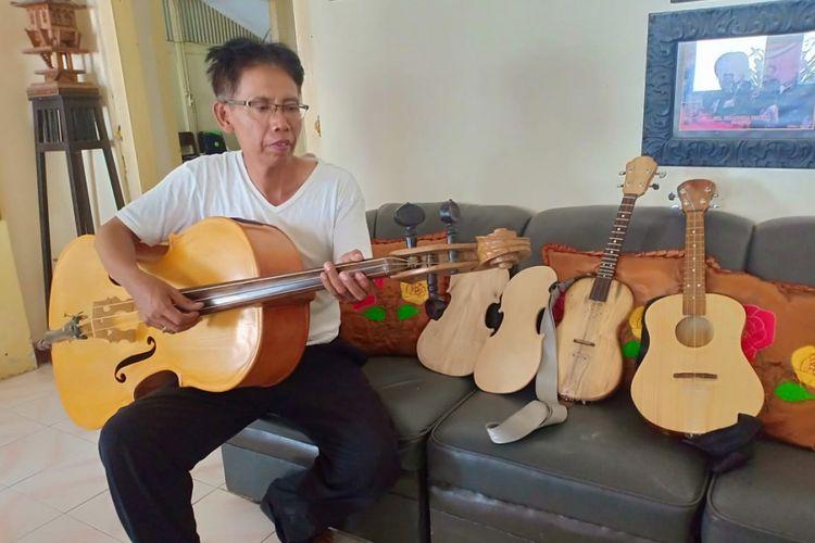 Erwan Prasetyo, seniman keroncong asal Madiun memainkan alat musik Cello hasil karyanya yang dibuat dari bahan kayu bekas peti kemas, Jumat ( 14/9/2018).