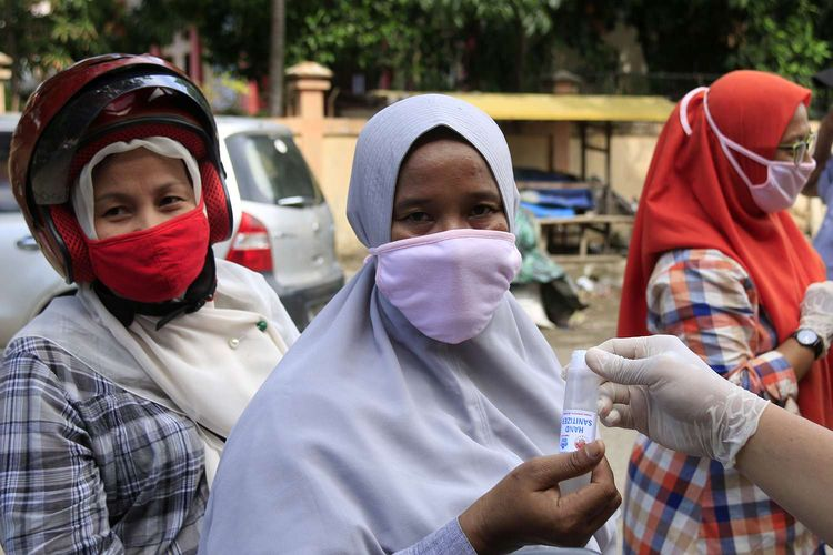 Komunitas etnis tionghoa yang tergabung dalam Yayasan Hakka Aceh membagikan masker dan hand sanitizer kepada pedagang kaki lima dan warga di pasar Peunayong,Kota Banda Aceh. Rabu (08/04/2020). 5000 masker dan hand sanitizer ini dibagikan secara geratif kepada pedagang kaki lima dan warga yang tidak memilki masker saat beraktifitas diluar rumah ini dilakukan sebagi aksi berbagi sesama untuk mencegah penyebaran wabah virus corona di Aceh, seperti himbauan pemerintah masyarakat wajib menggunkan masker saat melakukan aktivitas di luar rumah.