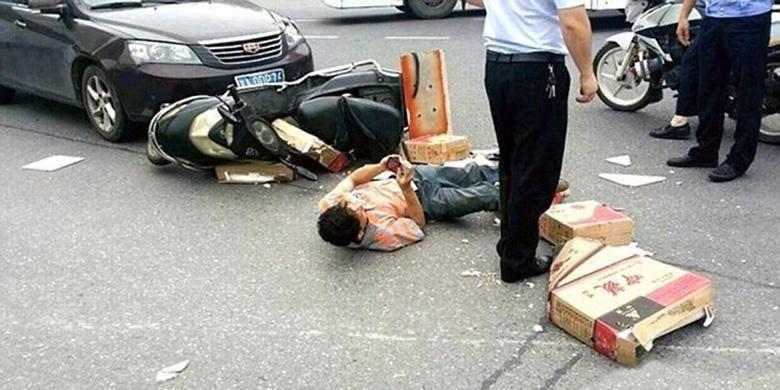 Pria Tiongkok di kota Changsa sibuk dengan ponselnya sambil terkapar di tengah jalan usai mengalami kecelakaan