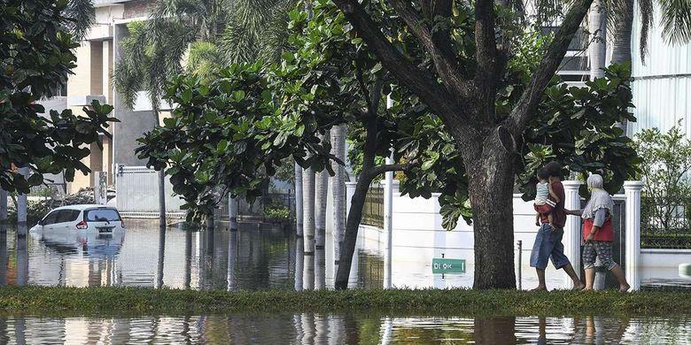 Warga melintas di Kompleks Pantai Mutiara yang tergenang banjir rob di Penjaringan, Jakarta, Minggu (7/6/2020). Banjir di kawasan tersebut diduga akibat adanya tanggul yang jebol saat naiknya permukaan air laut di pesisir utara Jakarta.