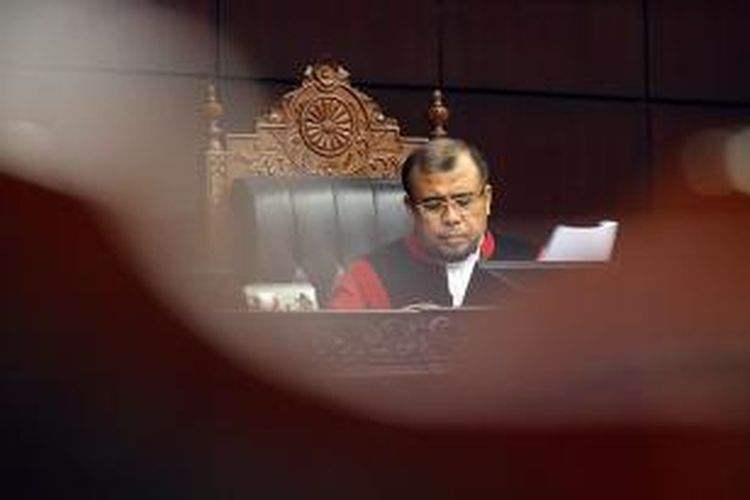 Hakim Konstitusi Patrialis Akbar bersama hakim lainnya meneruskan pembacaan putusan sengketa pilkada di Mahkamah Konstitusi, Jakarta, Kamis (14/11/2013). Sebelumnya sidang putusan sengketa Pilkada Maluku berlangsung ricuh, massa yang diduga berasal dari pasangan penggugat, Herman Adrian Koedoeboen dan Daud Sangadji, menyerbu masuk ke dalam ruang sidang saat mendengar gugatan mereka ditolak.