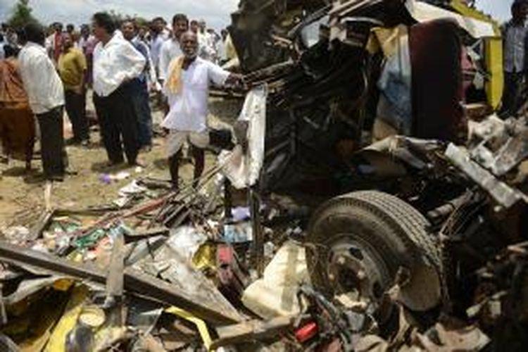 Warga melihat sisa bus sekolah yang hancur dihantam kereta api di negara bagian Telangana, India, Kamis (24/7/2014). Kecelakaan ini menewaskan 20 orang yang sebagian besar adalah anak-anak.