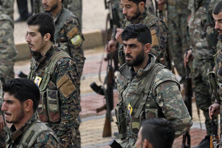 Para perjurit Tentara Demokratik Suriah (SDF) yang membantu AS memerangi ISIS  menghadiri pemakaman rekan mereka yang gugur di medan tempur, di kota berpenduduk mayritas etnis Kurdi Qamishli.