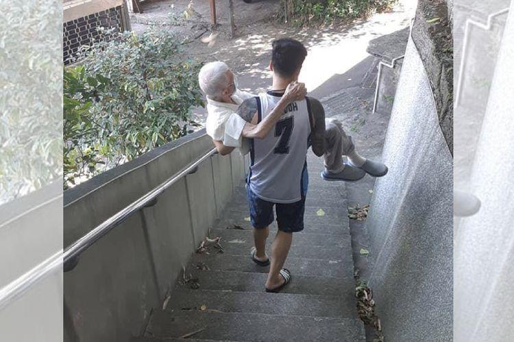 Foto tak bertanggal yang menunjukkan seorang pemuda menggendong kakeknya menuruni bukit menuju tempat vaksinasi di Keelung, Taiwan.