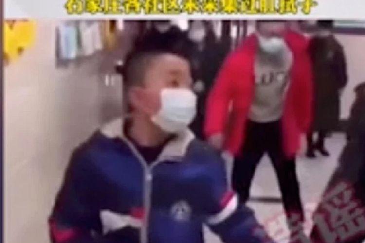 Potongan video yang beredar di China memerlihatkan seorang anak berjalan bersama orangtuanya, sementara di belakangnya ada pria yang berjalan seperti penguin. Narasi dalam video yang beredar adalah warga berjalan seperti itu setelah mendapatkan swab di bagian anus. Narasi tersebut membuat pemerintah setempat buka suara dan menyebut kabar itu tidak benar.(Screengrab from YouTube)