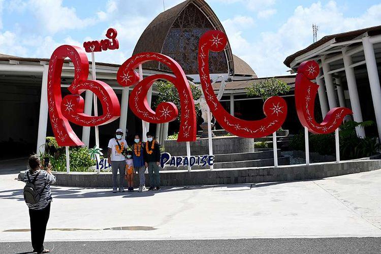 Penumpang berfoto di Bandara Internasional I Gusti Ngurah Rai, Badung, Bali, pada hari pertama dibukanya kembali kunjungan wisatawan domestik, Jumat (31/7/2020). Pemerintah Provinsi Bali mulai membuka sektor pariwisata bagi wisatawan domestik pada Jumat (31/7) dengan sejumlah persyaratan yang mengedepankan aspek kesehatan dan kualitas untuk memberi pelindungan, kenyamanan dan keamanan bagi wisatawan yang berkunjung selama masa pandemi Covid-19.