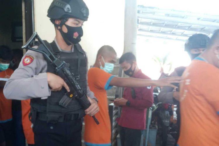 Polisi bersenjata lengkap menggiring komplotan pengedar narkoba yang diringkus Satres Narkoba Polres Cianjur.