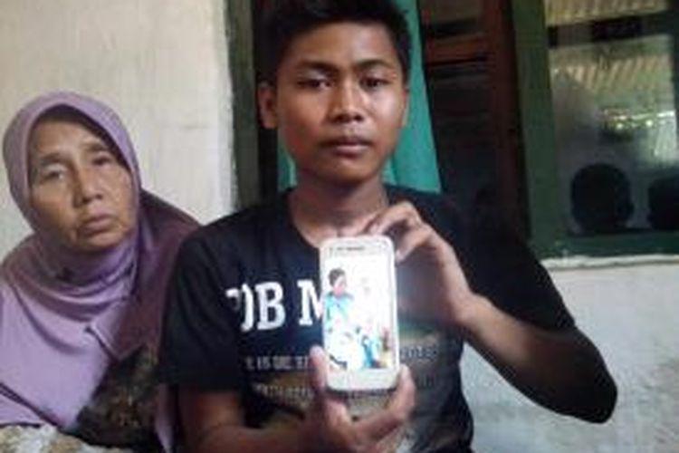 Keluarga menunjukkan foto almarhum  Suniyem  yang menjadi  tewas dalam  kecelakaan bis Harapan Jaya  di Waru, Sidoarjo, Jawa Timur, Senin (13/10/2014).