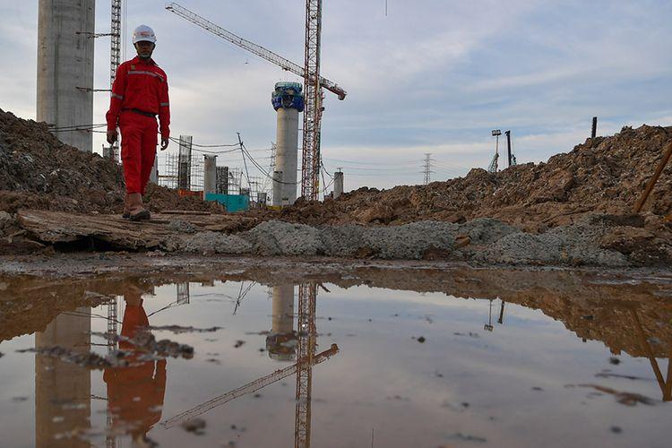Pekerja melintas di proyek pembangunan Jakarta International Stadium atau Stadion Bersih, Manusiawi dan Wibawa (BMW) di kawasan Papanggo, Tanjung Priok, Jakarta, Selasa (10/3/2020). Saat ini pembangunan proyek Stadion BMW yang akan memiliki kapasitas 80 ribu penonton tersebut telah mencapai tahap pekerjaan struktur bagian bawah dan struktur atas dengan persentase 19,6 persen.